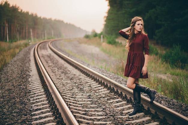 Mooi droevig nadenkend meisje met krullend natuurlijk haar op aard in bos op spoorweg