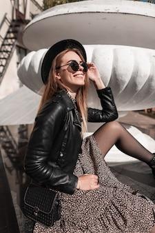 Mooi elegant jong lachend meisje met zonnebril in een modieuze leren jas en vintage jurk met zwarte tas zit buiten op een zonnige dag