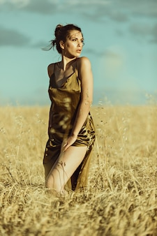 Mooi elegant model bij zonsondergang in een maïsveld met elegante jurk