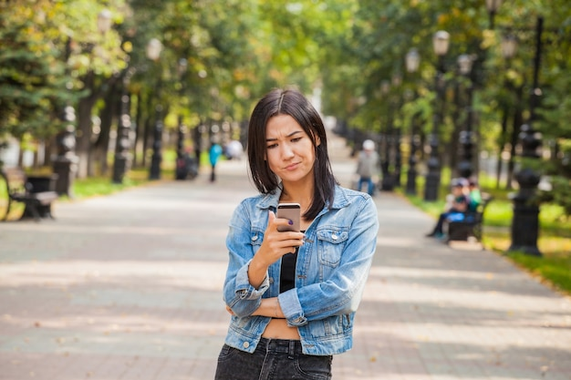 Mooi emotioneel aziatisch meisje met een smartphone in haar handen. droefheid