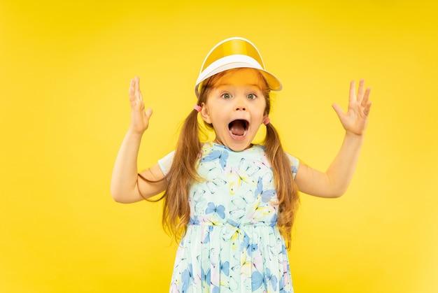 Mooi emotioneel geïsoleerd meisje. portret van een blij en verbaasd kind dat een jurk en een oranje pet draagt. concept van de zomer, menselijke emoties, kindertijd.