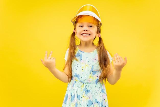 Mooi emotioneel meisje dat op gele achtergrond wordt geïsoleerd. halflang portret van een gelukkig en feestend kind dat een jurk en een oranje pet draagt. concept van de zomer, menselijke emoties, kindertijd.