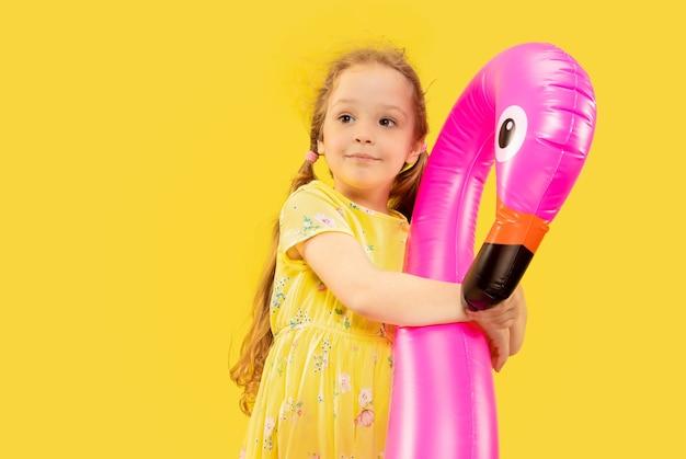 Mooi emotioneel meisje dat op gele achtergrond wordt geïsoleerd. halflang portret van een gelukkig kind dat een jurk draagt en een rubberen roze flamingo vasthoudt. concept van de zomer, menselijke emoties, kindertijd.