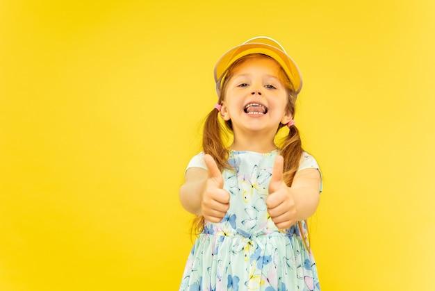 Mooi emotioneel meisje dat op gele achtergrond wordt geïsoleerd. halflang portret van een gelukkig kind dat een jurk en een oranje pet draagt die een gebaar van ok toont. concept van de zomer, menselijke emoties, kindertijd.