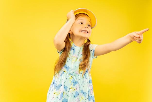 Mooi emotioneel meisje dat op gele achtergrond wordt geïsoleerd. halflang portret van een gelukkig kind dat een jurk en een oranje pet draagt die naar boven wijst. concept van de zomer, menselijke emoties, kindertijd.