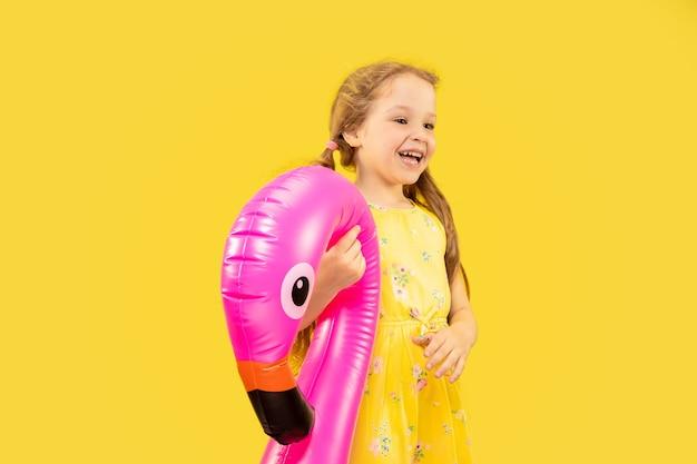 Mooi emotioneel meisje dat op gele ruimte wordt geïsoleerd. halflang portret van een gelukkig kind dat een jurk draagt en een rubberen roze flamingo vasthoudt