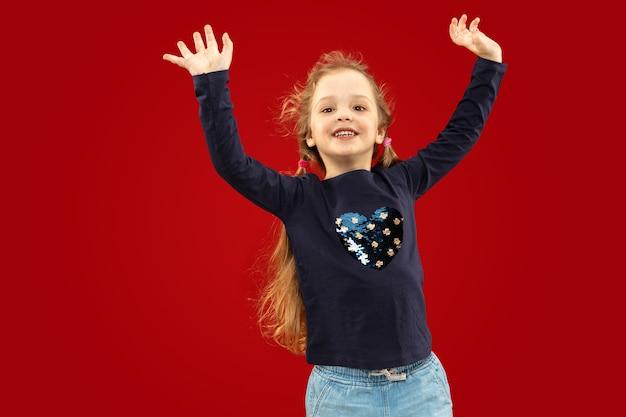 Mooi emotioneel meisje dat op rode ruimte wordt geïsoleerd. halve lengte portret van gelukkig en kind glimlachend en dansen
