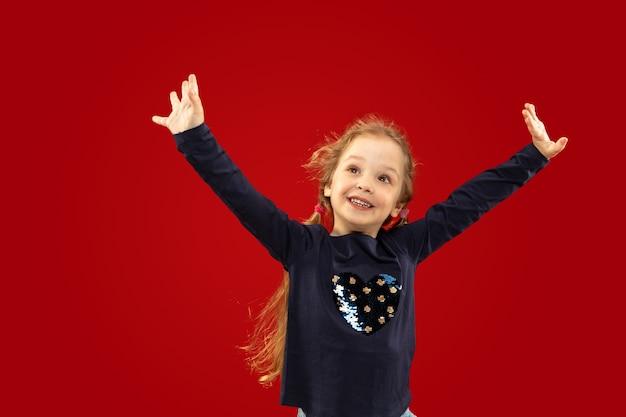 Mooi emotioneel meisje dat op rode studio wordt geïsoleerd