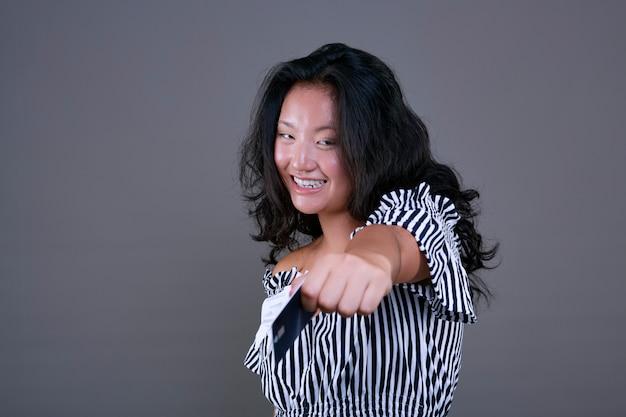 Mooi en aardig jong chinees meisje dat kaart aanbiedt met directe blik en glimlach