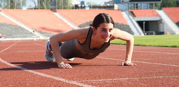 Mooi en atletisch meisje push-ups in het stadion