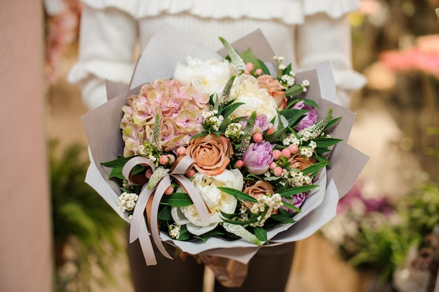 Mooi en delicaat boeket van kleurrijke bloemen in handen