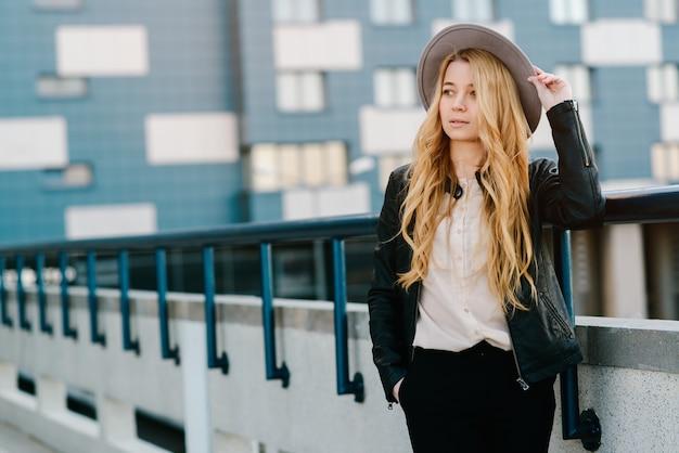 Mooi en jong meisje dat in hoed in de stad loopt