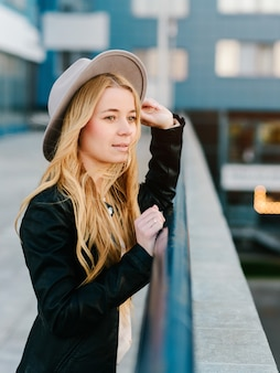 Mooi en jong meisje in een hoed die in de avondstad loopt
