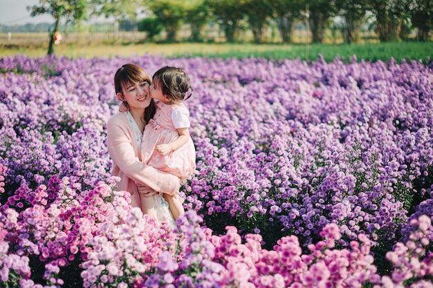 Mooi en romantisch beeld van moeder en haar kleine kinderen die samen in de bloementuin spelen.