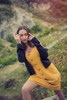 Mooi en schattig meisje in de buurt van kleurrijke gebladertestruik in een park, herfstatmosfeer