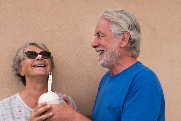 Mooi en schattig paar van twee senioren die samen plezier hebben met milkshake of ijs - volwassen vrouw met ijs op haar neus en volwassen man lachen