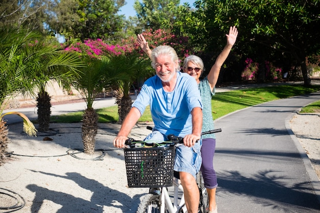 Mooi en schattig paar volwassen en oude vrouw en man samen rijden op een dubbele fiets in een groen park met roze bloemen op de achtergrond. actieve senior die plezier heeft met tandem