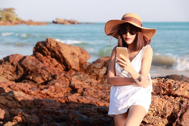 Mooi en schattig zakenvrouw met behulp van mobiele telefoon met zonnebril en hoed op het strand
