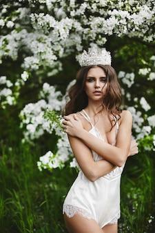 Mooi en sexy jonge model vrouw met perfecte lichaam in stijlvolle lingerie met de kroon op haar hoofd poseren onder de bloeiende boom op groen bos