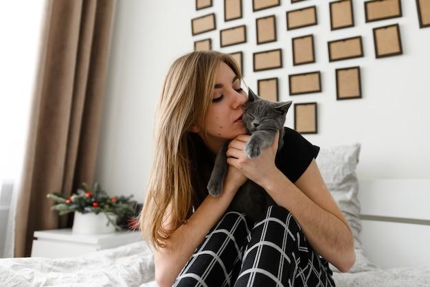 Mooi en sexy meisje liggend op het bed in zelfgemaakte pyjama's met een gelukkig schots grijs katje in haar armen.