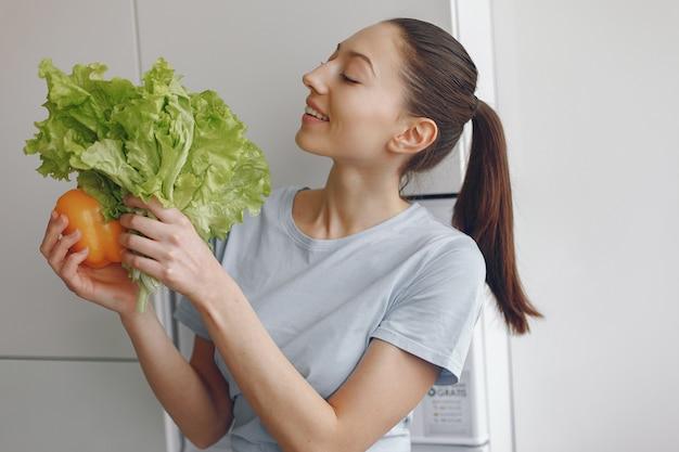 Mooi en sportief meisje in een keuken met groenten