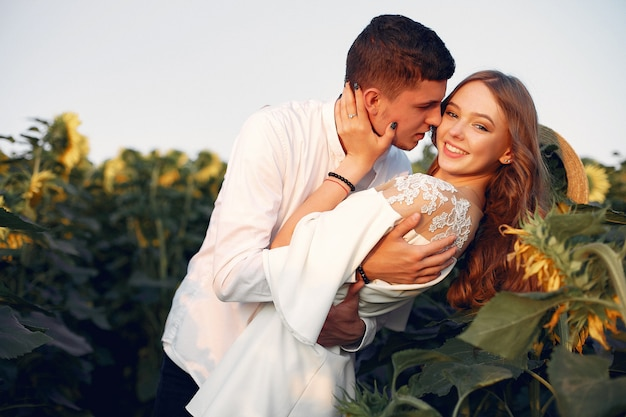 Mooi en stijlvol paar in een veld met zonnebloemen