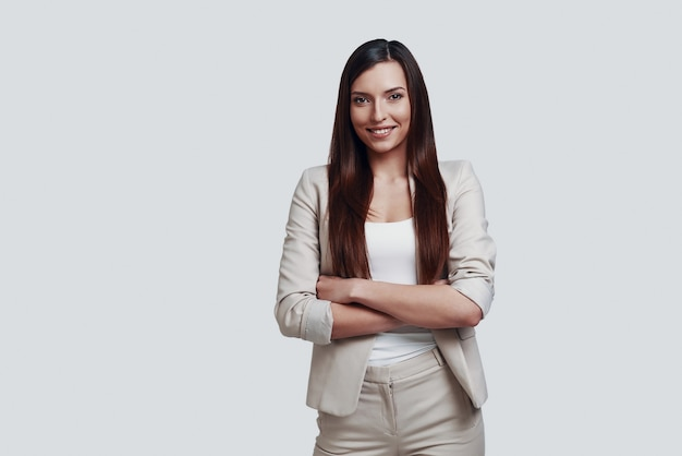 Mooi en succesvol. aantrekkelijke jonge vrouw die naar de camera kijkt en glimlacht terwijl ze tegen een grijze achtergrond staat