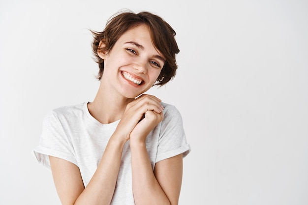 Mooi en teder meisje zonder make-up, glimlachend en kijkend naar iets schattigs en schattigs, witte muur