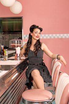 Mooi en vriendelijk pinup-meisje in een restaurant uit de jaren 50