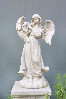 Mooi engelenstandbeeld tegen grijze muurachtergrond.