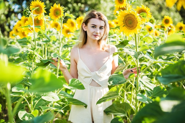 Mooi europees meisje in een witte jurk op aard met zonnebloemen