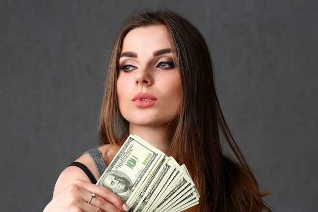 Mooi europees vrouwenportret. verspreidend geld merkt dollars op in mode-geloften stijl krullend haar met witte lokken oogzicht van de camera