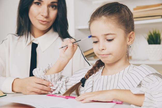Mooi familieconcept. moeder en dochter zitten samen en studeren thuis.