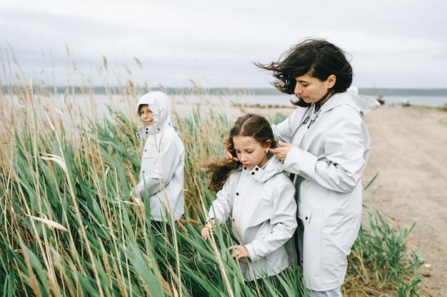 Mooi familieportret gekleed in regenjas dichtbij het meer