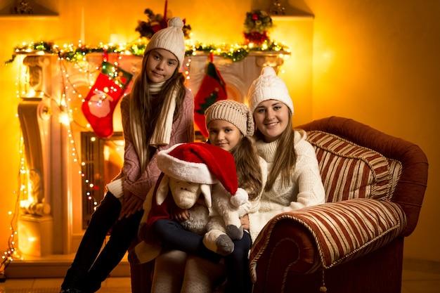 Mooi familieportret tegen open haard op kerstavond bij huis