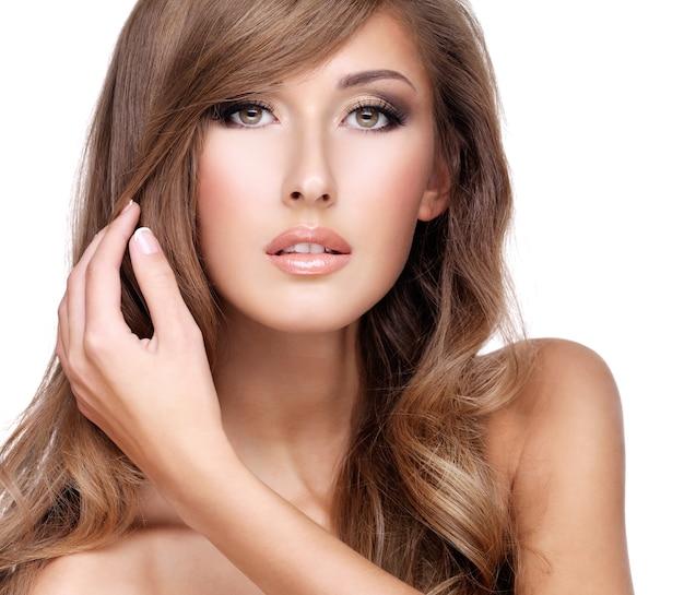 Mooi fasionmodel raakt haar schitterende lange haar, dat op wit wordt geïsoleerd
