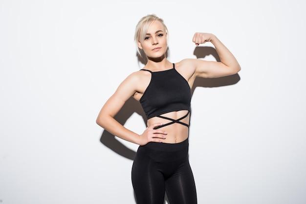 Mooi fit vrouwelijk model in zwarte passende kleding die zich voordeed over wit