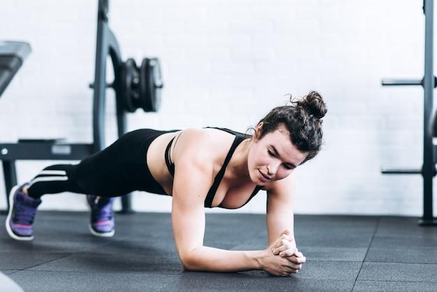 Mooi fitness meisje maken plank oefeningen op de vloer in de sportschool