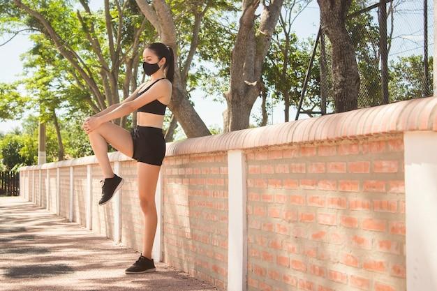 Mooi fitness meisje met een gezichtsmasker doet zich het uitrekken in het park nieuwe normaal