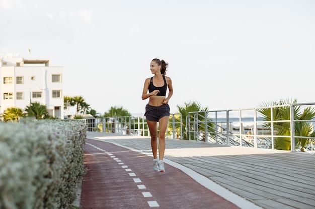 Mooi fitnessmeisje in korte broek en sporttop die bij zonnig weer aan de waterkant aan zee loopt