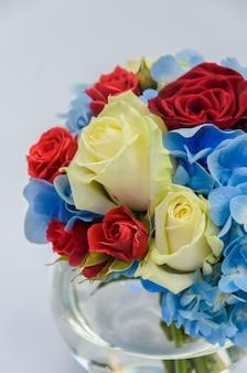 Mooi fris helder boeket van blauwe hortensia's, rode en crème rozen in een ronde glazen vaas op een witte tafel. mooie bloemensamenstelling.
