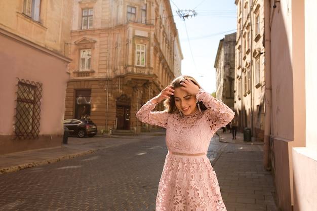 Mooi gebruind model poserend in modieuze kleding op straat