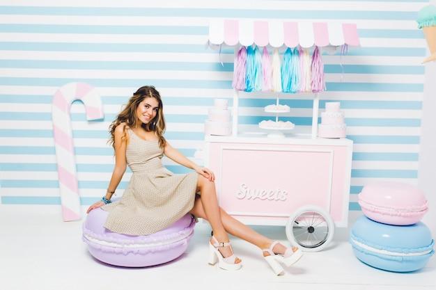 Mooi gelooid meisje dat vintage jurk draagt, zittend op een paarse stoel die eruit ziet als een macaron in de buurt van de snoepwinkel. indoor portret van bevallige vrouw met glanzend haar koelen naast patisserie.