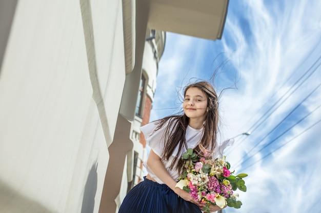 Mooi gelukkig babymeisje dat met boeketten bloemen door de stad loopt