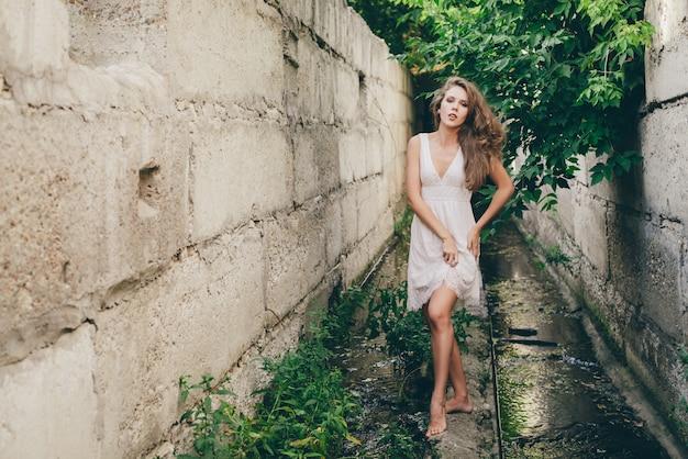 Mooi gelukkig dansend meisje met krullend natuurlijk haar in witte kleding dichtbij groene boombladeren