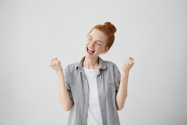 Mooi gelukkig europees meisje dat zich opgewonden en gelukkig voelt, ogen stijf sluit van plezier, mond openhoudt en gebalde vuisten