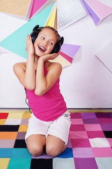 Mooi gelukkig kindmeisje dat aan muziek en het zingen luistert.