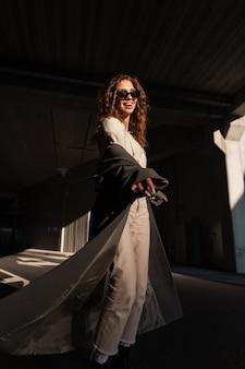 Mooi gelukkig krullend meisje met een glimlach in een modieuze lange jas en beige kleding loopt op straat op een achtergrond van een donkere stedelijke achtergrond. grappig stijlvol vrouwenmodel
