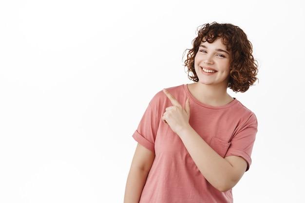 Mooi gelukkig meisje, glimlachend met witte tanden, wijzend naar de linkerbovenhoek en kopieerruimte op wit tonen