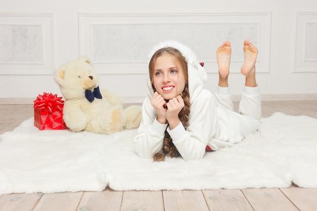 Mooi gelukkig meisje in pyjama dat op de vloer ligt